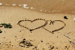 two hearts drawn in sand on beach the kindness zone making relationships work